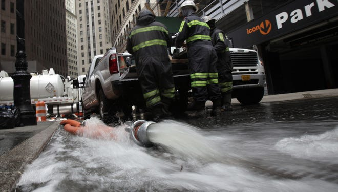 Water is pumped from a subterranean parking garage in New York's Financial District on Friday.
