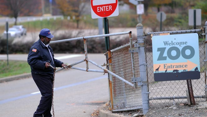 A security guard closes the gate at the Pittsburgh Zoo, where zoo officials say a young boy was killed after he fell into the exhibit that was home to a pack of African painted dogs.