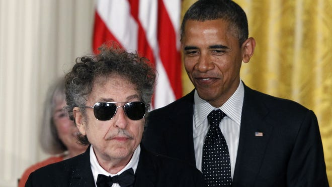 President Barack Obama stands with  Bob Dylan before awarding Dylan the Medal of Freedom during a ceremony in the East Room of the White House in Washington.