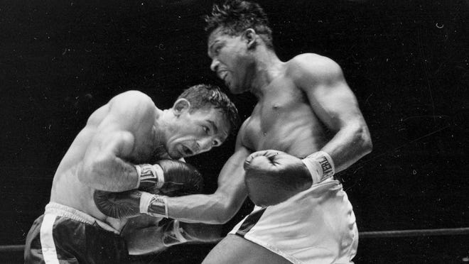 This 1957 file photo shows world middleweight champion Sugar Ray Robinson, right, fighting challenger Carmen Basilio in the fifth round of a title fight at Yankee Stadium. Basilio, who wrested the title from Robinson, has died. He was 85.