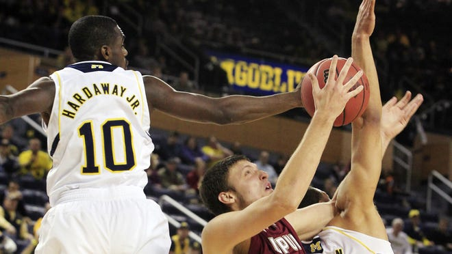 IUPUI center Mitchell Patton (42) is defended by Michigan guard Tim Hardaway Jr., (10) and forward Jordan Morgan (52). The Wolverines beat IUPUI 91-54 and have scored at least 90 points in both games this season.