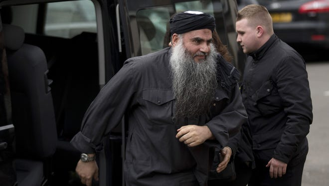 Abu Qatada, left, gets out of a vehicle after returning to his residence in London on Tuesday.