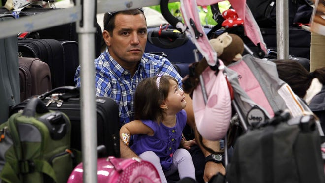 In this Nov. 23, 2011, file photo, Jose Mendes waits in line with his daughter Maria Celeste at Miami International Airport before the Thanksgiving holiday weekend.