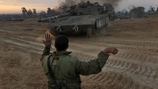 An Israeli soldier guides a tank to a new position at a staging area near the Israel Gaza Strip Border on Nov. 22.