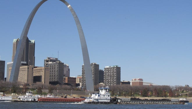 Two barges head north on the Mississippi River past St. Louis, as seen from East St. Louis, Ill.