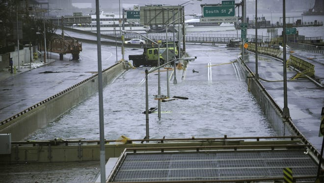 Water flows onto the street at the flooded Battery Park Underpass on Oct. 30 in New York.