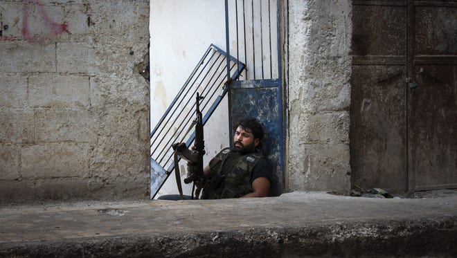 Mustafa, a rebel from the town of Bennish, watches for a sniper firing down a street in Harem, Syria.