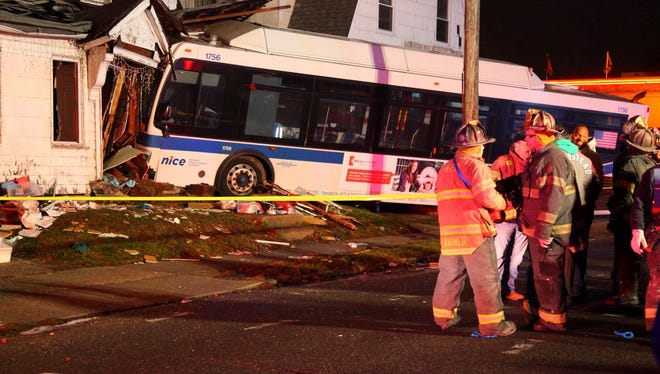 Firemen work the scene where a  Nassau County bus, attempting to avoid hitting a pedestrian, crashed into a multifamily house.