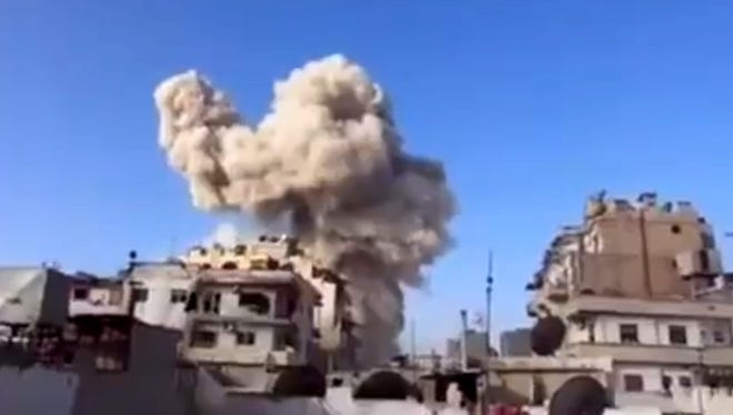 Smoke leaps from a building after a warplane attack in Homs, Syria on Wednesday.
