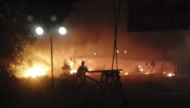 In this Nov. 29 photo provided by a monk, flames are seen at the gate of Chinese mining partner Wan Bao, where protesters camped before the police crackdown in northwestern Burma.