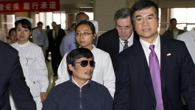 Chen Guangcheng, center, holds hands with U.S. Ambassador to China, Gary Locke, right, at a hospital in Beijing where he recuperated after he fled house arrest from his hometown in northeast China.