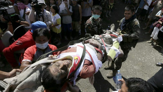 A survivor of Tuesday's devastating typhoon is carried into a makeshift clinic after being rescued