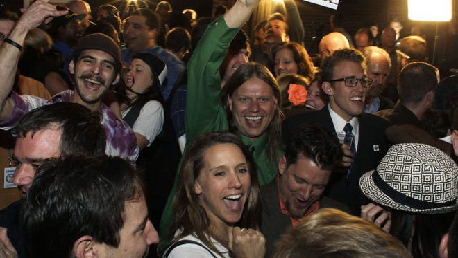 People attend an Amendment 64 watch party to celebrate after a local television station announced the marijuana amendment's passage in Denver.