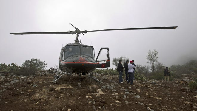 A rescue helicopter sits on top of the hill right next to the canyon where U.S.-born singer Jenni Rivera's jet crashed near the town of Iturbude, Mexico, on Monday.