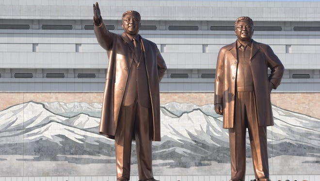 North Koreans bow before the statues of late leaders, Kim Il Sung, left, and Kim Jong Il, at Mansu Hill in Pyongyang, North Korea, Dec. 17. Sirens wailed for three minutes at noon Monday in honor of the first anniversary of the death of Kim Jong Il.