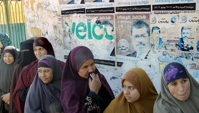 Egyptian women line up to vote in Giza, Egypt, Saturday during the second round of a referendum on a disputed constitution drafted by Islamist supporters.