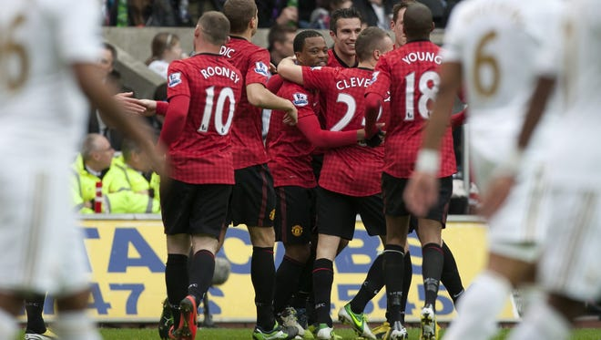 Manchester United's Patrice Evra, center, celebrates with teammates after scoring against Swansea.