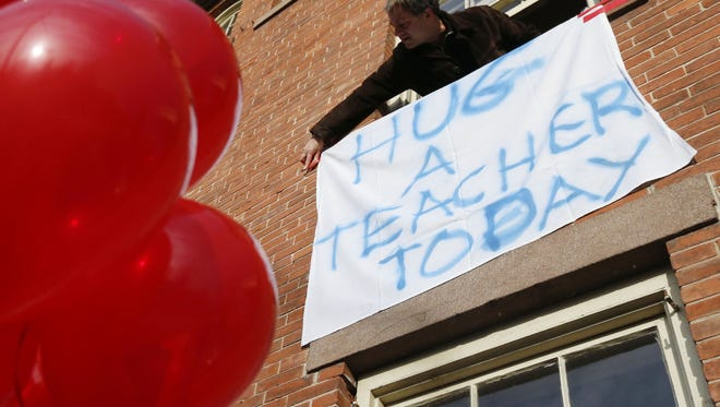 """Gary Seri hangs a sign reading """"HUG A TEACHER TODAY"""" written on a table cloth in honor of the teachers who died along with students when a gunman opened fire at a school in Newtown, Conn."""