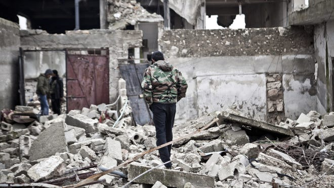 Free Syrian Army fighters walk amid the ruins of a village Saturday.