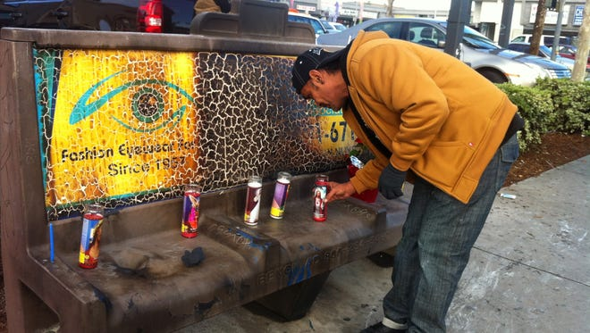 Phil Furtado places candles on a burned city bus bench in Los Angeles on Thursday.