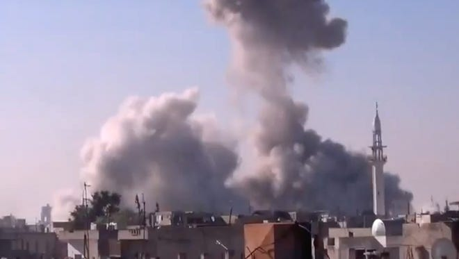 In this image taken from video obtained from the Shaam News Network, which has been authenticated based on its contents and other AP reporting, smoke rises from buildings from heavy shelling in Homs, Syria, on Thursday.