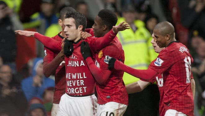 Manchester United's Robin van Persie, centre left, celebrates with teammates after scoring against West Brom.