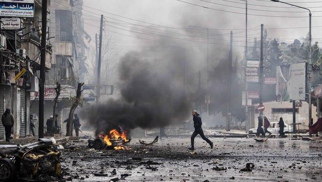 A man runs between debris after a mortar shell hit a street killing several people in the Bustan Al-Qasr district of Aleppo, Syria, on Dec. 17.