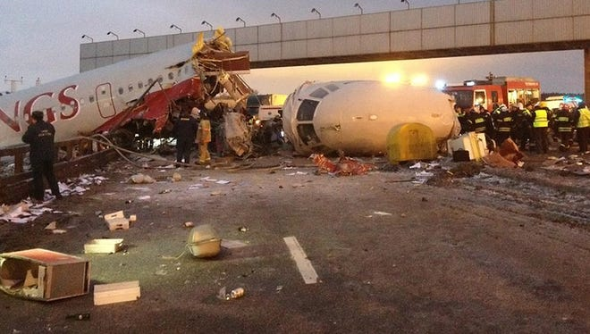 Rescuers work at the site of careered off the runway plane at Vnukovo Airport in Moscow, Saturday.