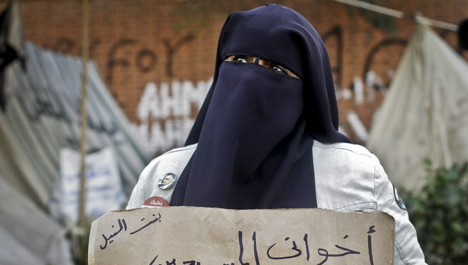 """An Egyptian woman holds a poster with Arabic that reads, """"my Christian siblings.. happy new year.."""" in front of the presidential palace in Cairo, Egypt, Monday."""