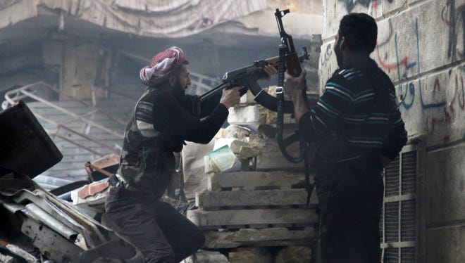 Free Syrian Army fighters fire at enemy positions during heavy clashes with government forces Saturday, in the Salaheddine district in Aleppo, Syria.