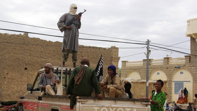 In this Aug. 31, 2012 file photo, fighters from Islamist group Ansar Dine stand guard in Timbuktu, Mali, as they prepare to publicly lash a member of the Islamic Police found guilty of adultery.