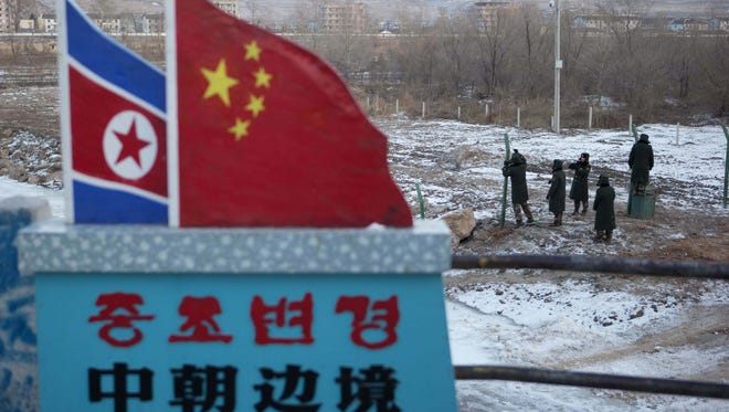 "Chinese paramilitary policemen build a fence near a concrete marker depicting the North Korean and Chinese national flags with the words ""China North Korea Border"" at a crossing in the Chinese border town of Tumen in eastern China's Jilin province."