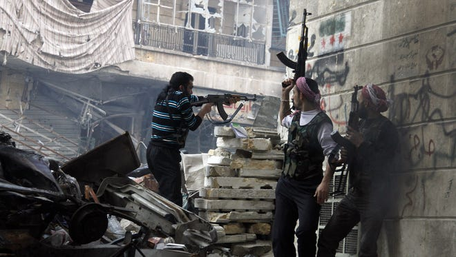 Free Syrian Army fighters fire at enemy positions during heavy clashes with government forces.