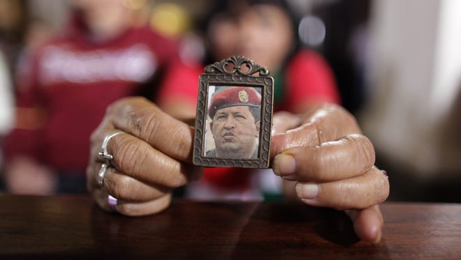 A woman holds a picture of Venezuela's President Hugo Chavez as people gather to pray for him at a church in Caracas, Venezuela,  on Monday.