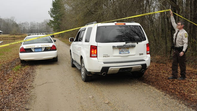 A Walker County sheriff's deputy lifts crime scene tape for investigators Wednesday as National Transportation Safety Board officials continue to investigate the fatal crash of a small plane near Jasper, Ala.