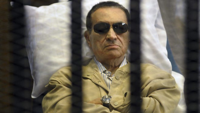 Egypt's former president Hosni Mubarak lies on a gurney inside a barred cage in the police academy courthouse in Cairo.