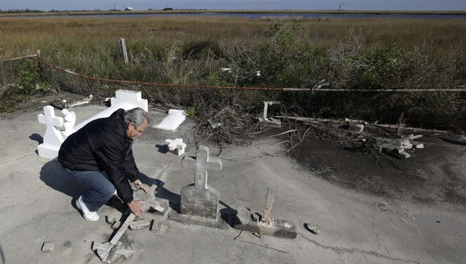South Lafourche Levee District General Manager Windell Curole handles pieces of headstone at his small family cemetery, which sits along the bayou near Leeville, La.