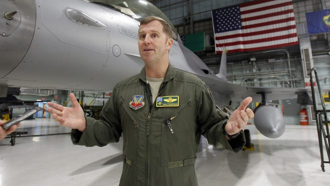 Lt. Col. Dan Finnegan stands by an F-16 fighter plane as he's interviewed in South Burlington, Vt, on Dec. 17.