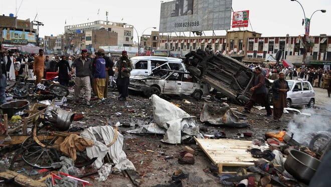 Pakistani police officers and local residents gather at the site of bombing in Quetta, Pakistan, on Thursday.