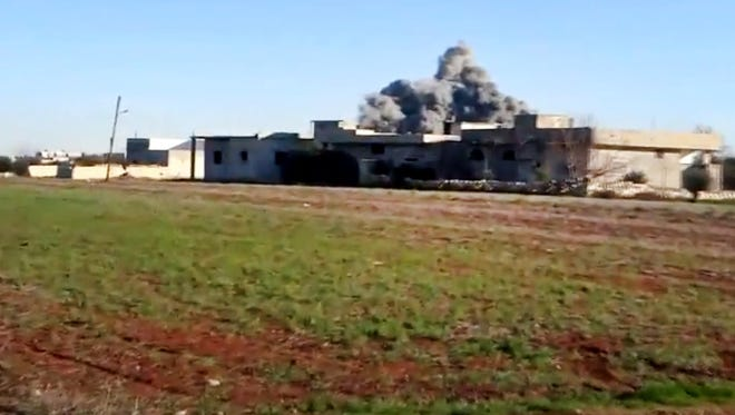 Smoke rises over a building due to heavy shelling in Taftanaz, Idlib province, northern Syria.