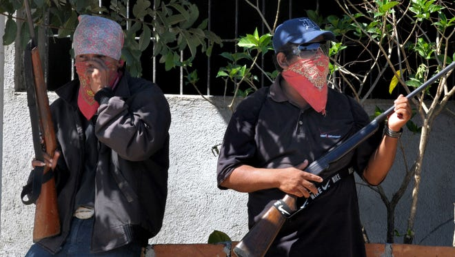 People wearing bandanas and carrying small arms man a checkpoint in Teconoapa, in the Mexican state of Guerrero, Friday.