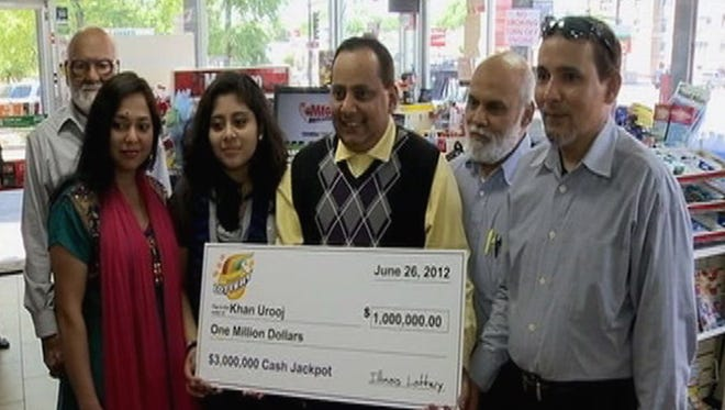 Urooj Khan, center, holds a ceremonial check in Chicago for $1 million as winner of an Illinois instant lottery game.