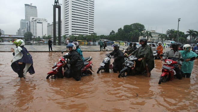 Indonesians push their motorcycles through a flooded street in Jakarta, Indonesia, on Thursday.
