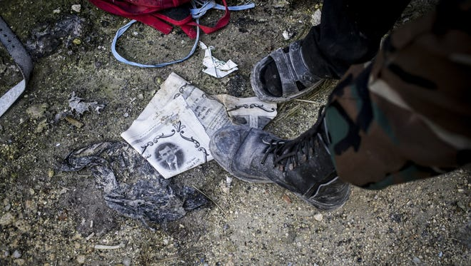 A Free Syrian Army fighter steps on a paper with the photo of Syrian President Bashar Assad in Aleppo.