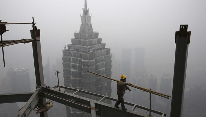 A worker carries steel bars on top of the construction site of Shanghai Tower while the skyscrapers in the Pudong area are shrouded in the heavy fog in Shanghai, China.