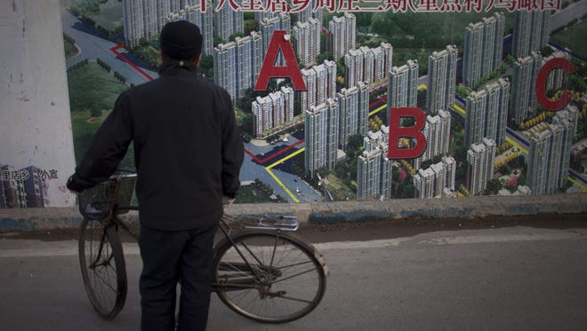 A man stops his bicycle to check an artistic rendering of a residential real estate project outside the construction site in Beijing, China, Jan. 17, 2013.