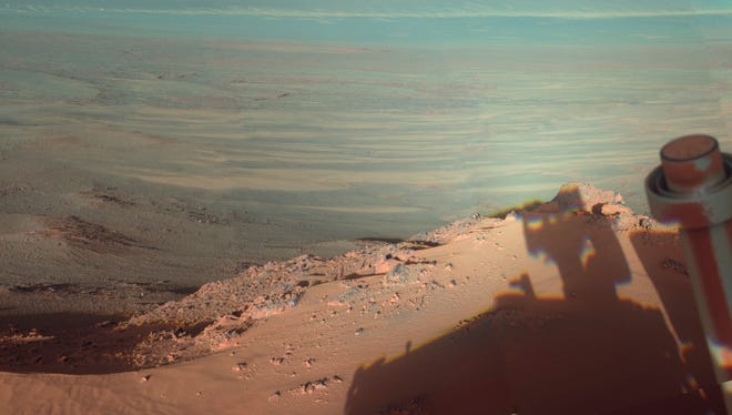 This image provided by NASA shows the late-afternoon shadow cast by the Mars rover Opportunity at Endeavour Crater. The six-wheel rover landed on Mars in January 2004 and is still going strong.
