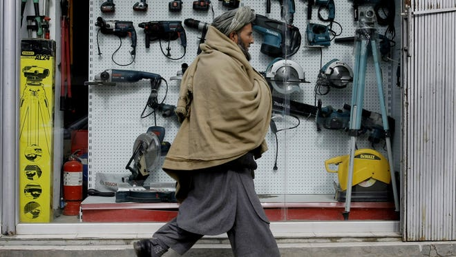 An Afghan man walks past a shop selling tools made in China in Kabul, Afghanistan on Tuesday.