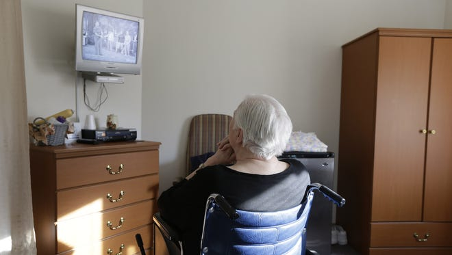 An elderly woman who was abused by a relative watches television Jan. 8 inside her room at Cedar Village retirement community in Mason, Ohio.