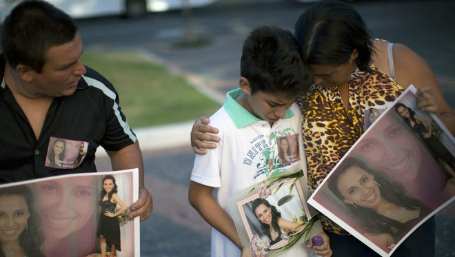 Relatives hold photographs of Pamella Lopes, who died in the nightclub fire in Santa Maria, Brazil.